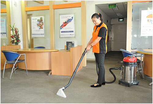 A professional carpet cleaning service cleans an office carpet using a vacuum cleaner